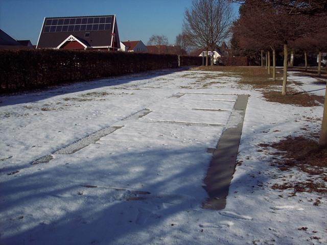NDas Bild zeigt die gerade teilweise mit Schnee bedeckten umlaufenden Boden-platten der 5 vorbereiteten Felder für die Doppelgräber der neuen Generation.